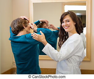 Ophthalmologist Assisting Woman To Insert Contact Lens -...