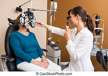 Optometrist Examining Senior Womans Eyes - Young female...