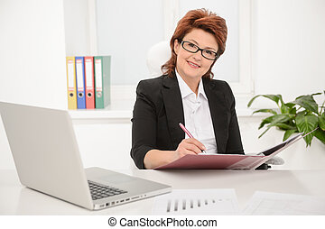 Adult businesswoman working on documents in office -...