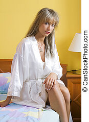 sitting on the bed - cute blond woman in nightgown sitting...