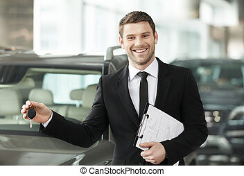 Great choise Handsome young classic car salesman standing at...