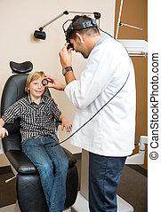 Optician Examining Boy's Eye Through Lens - Male optician...