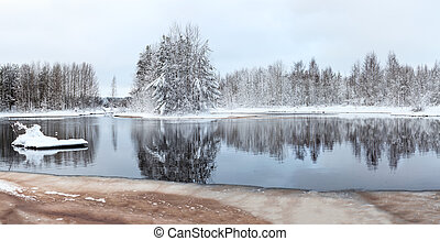 Mid size panorama of unfrozen winter lake with snow-covered...