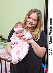 Loving young mother holding her baby in hands