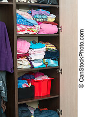 Various color clothes at shelves in wardrobe