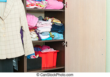 Various color clothes are organized at shelves in open...
