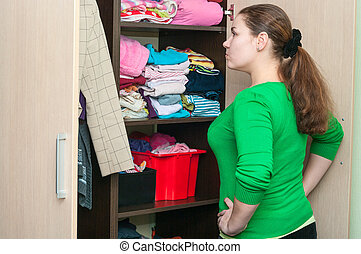 Young caucasian woman in the wardrobe selecting things for...