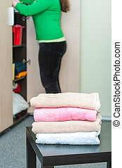 Stack of towels on table in foreground and housewife in...
