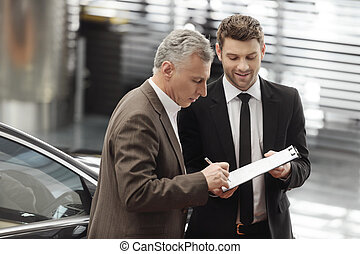 Please, sign hear Handsome young car salesman helping his...