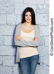 Young beautiful happy woman in casual cloths against brick...