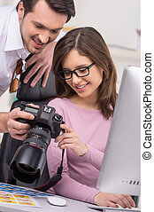 Man showing photo to a nice woman in glasses. Casual outfit,...