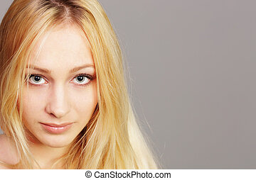 closeup portrait of a young blonde girl on gray background
