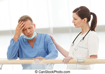 Depressed surgeon. Young female doctor comforting her depressed colleague in blue uniform