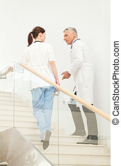 Discussing the current problems. Hospital colleagues talking to each other while going upstairs