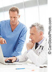 Discussing medical reports. Mature doctor using computer and discussing medical reports with his colleague