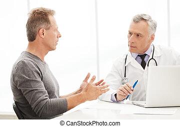 Doctor and patient Doctor listening to the patient while he...