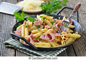 Pasta with ham and bacon, cheese and eggs in a pan