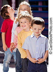 Boy Standing With Friends In A Row At Kindergarten -...