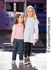 Girl Standing Arms Around With Female Friend In Kindergarten...