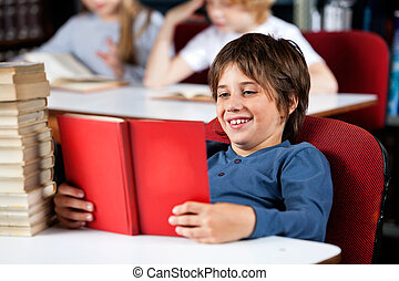 Schoolboy Smiling While Reading Book At Table In Library -...