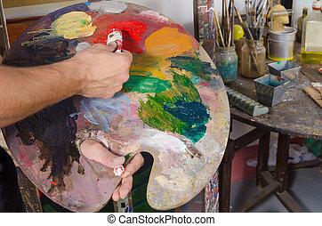 Painters palette - A painter preparing his palette agaist...