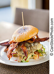 Bacon Burger on Plate in Restaurant - Fresh bacon burger on...