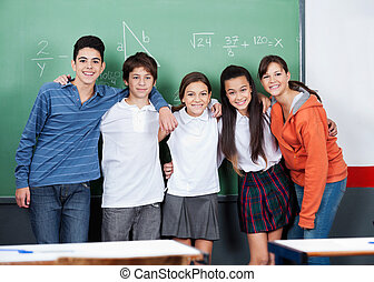 Teenage Friends Standing Together Against Board - Portrait...