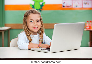 Girl Using Laptop In Classroom - Cute little girl using...
