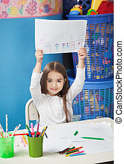 Girl Showing Drawing Paper In Art Class - Portrait of cute...