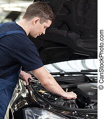 Auto mechanic at work. Confident auto mechanic working on...