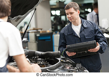 Mechanics at work shop. Two confident auto mechanics working...