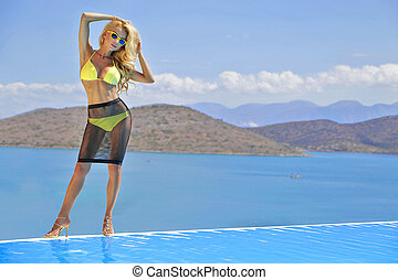 Beautiful woman lying by the pool i