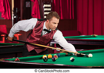 Man playing pool. Confident young man in bow tie playing...