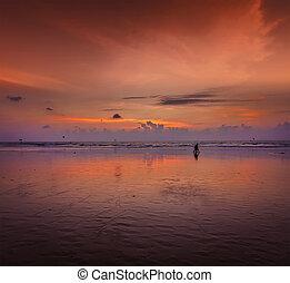 Romantic sunset, Goa, India - Couple walking on beach on...