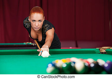 Sexy pool player. Beautiful young red hair woman playing...