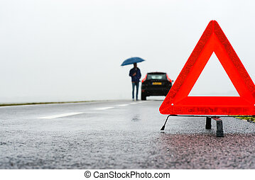 car with a breakdown in the rain and fog - man with an...