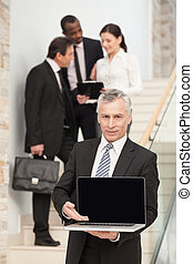 Mature businessman using laptop with executives at the back...