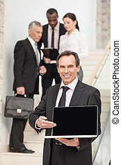 Middle aged business man using laptop with executives in the...