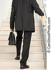 Rear view of a business person ascending the stairs - Rear...