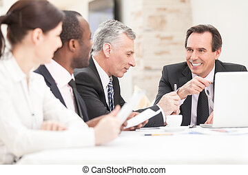 Smiling business people with paper work in board room -...