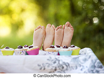 Happy kids - Two happy feet having picnic outside in summer