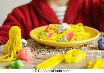 Portrait of child with plasticine spaghetti dish - Portrait...