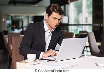 Handsome businessman working with laptop. Sitting at the...