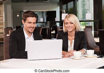 Business couple working with laptop at coffee While having...