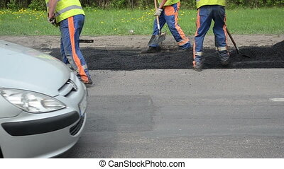 street work asphalt road - workers with shovel put hot...
