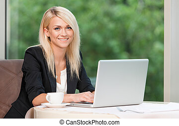 Smiling beautiful blond business woman with laptop. Drinking...