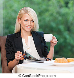 Attractive and stylish lady having breakfast. Reading...