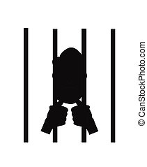 man behind bars in silhouette - jailed man holding onto bars...