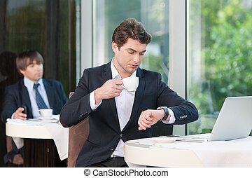 Busy businessman is looking at watch While drinking coffee