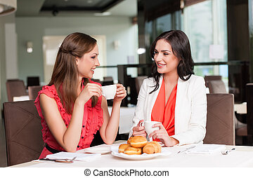 Two girlfriends meet at café for breakfast. Talking and gossiping